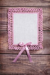 Napkin with pink lace on the wooden background