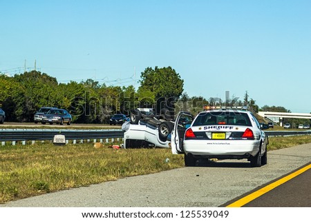 NAPLES, FL, USA - DECEMBER 22: A police car arrives at a car accident with the unidentified driver standing outside the vehicle. The event took place on DEC. 22, 2012 on HWY 75 in NAPLES, FL, USA .