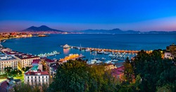 Naples, Italy. Beautiful sunset lights over the Naples' Bay with the marina in foreground and Mount Vesuvius far in the background.
