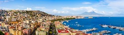 Naples, Italy: Panoramic view of the city and port with Mount Vesuvius on the horizon as  seen from the hills of Posilipo. Seaside landscape of the city harbor and golf on the Tyrrhenian Sea