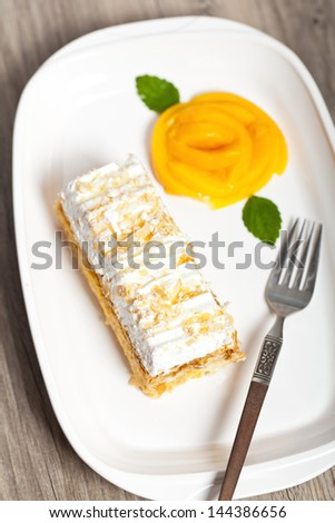 Napoleon cake with peaches and mint leaves