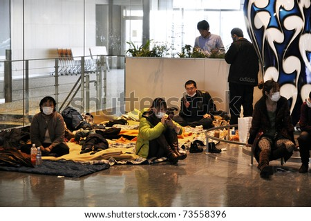 NARITA AIRPORT, JAPAN - MARCH 18 : People spend the night at Narita airport in Tokyo on March 18, 2011. Some wait for delayed or cancelled flights, others want to make sure they catch their flight.