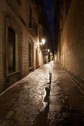Narrow alley at night in the Gothic Quarter (Barri Gotic) of Barcelona in Catalonia, Spain.