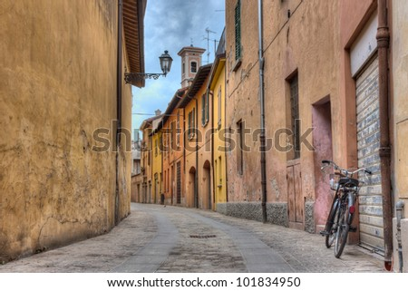 narrow alley in the old town with bicycle, street lamp and bell tower in Imola, Bologna, Italy
