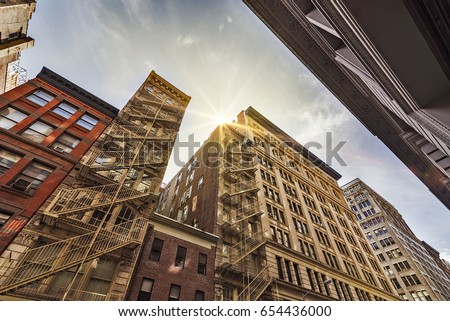 Narrow alley with Old apartment buildings and fire escapes on a sunny day in Midtown Manhattan, New York City #654436000