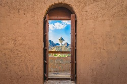 Narrow archway with old, heavy wooden doors opened to show the famous frankincense monument of Muscat, Oman
