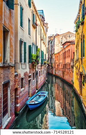 Narrow beautiful street with a lone boat, Venice, Italy. Scenic vertical view of Venice canal with reflection in water. Old houses and cityscape of Venice. Romantic water tourist trip across Venice. #714528121