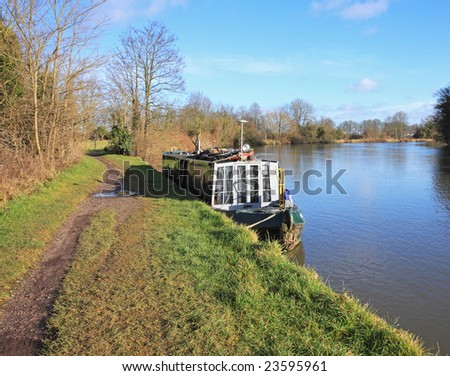 Narrow-boat moored on the banks of the River Thames England - stock photo