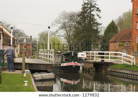 Narrow boat motoring through canal lock in village