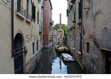 Narrow canal in Venice, Italy with old buildings and boats in the water #660241492
