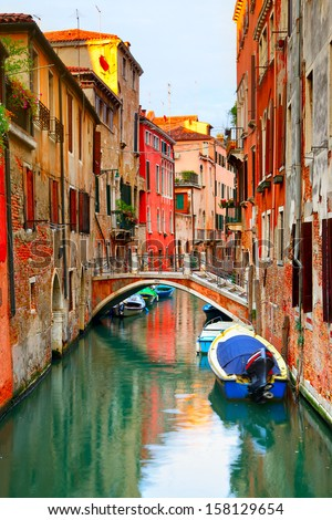 Narrow canal with boats in Venice, Italy