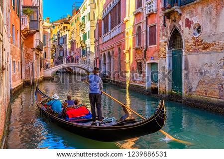 Narrow canal with gondola and bridge in Venice, Italy. Architecture and landmark of Venice. Cozy cityscape of Venice. #1239886531