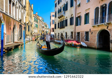 Narrow canal with gondola and bridge in Venice, Italy. Architecture and landmark of Venice. Cozy cityscape of Venice. #1291662322