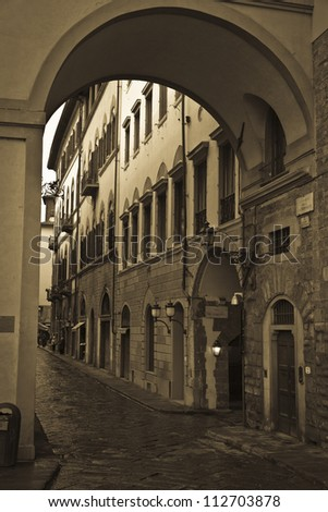 Narrow cobbled street of Florence Italy in sepia.