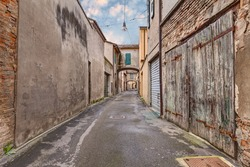 narrow dark alley in the old town - grunge aged street  - distressed alleyway in the italian city