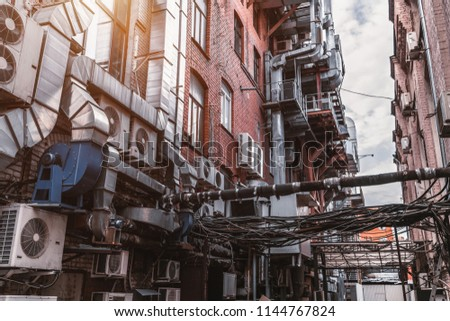 Narrow dark atmospheric backstreet between two old brick factory buildings with a huge amount of wires, outdoor air conditioning units, and plenty of ventilation tubes on the walls