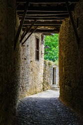 Narrow dark passageway made of ancient stone that leads to medieval house. Santillana del Mar.