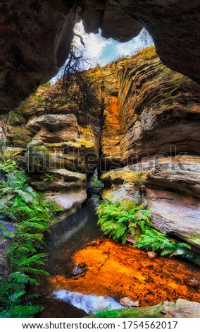 Narrow deep well in sandstone rocks of BLue Mountains national park, Australia - waterhall on Grand Canyon Walls walk.