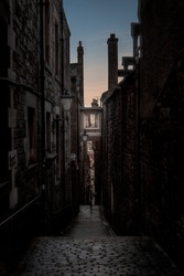 Narrow European alley, surrounded by bricks and cobblestone. Illuminated only with weak light from sunrise. Concept of scared or being alone and frightened
