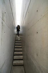 Narrow exposed concrete stair, lighting at the end of small corridor and silhouette man express to minimal style of architecture.