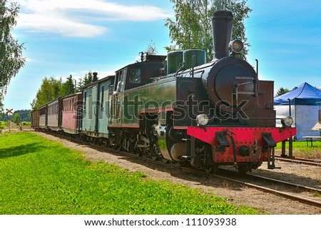 Narrow-gauge steam train pulling passenger carriages with tourists. Minkio, Finland