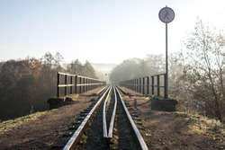 Narrow gauge train tracks passes over bridge with sign no trespassing and morning fog in Ankysciai, Lithuania