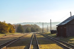 Narrow gauge train tracks passes wooden building and winds to morning fog covered forest in Ankysciai, Lithuania