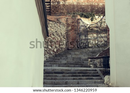 Narrow lane of European historic town with stone staircase. The path leads to the metal gate. Czech Republic, South Moravia, Mikulov.