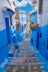 Narrow lane with steps in the blue medina of the Chefchaouen, Morocco. Blue city with traditional architecture in the Rif mountains of North Africa.