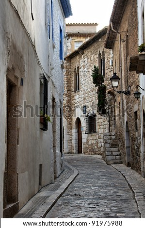 Narrow medieval street in Old Sigest town, historical resort-city close to Barcelona city, Spain