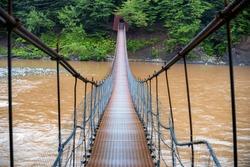 Narrow metal foot bridge across river in autumn