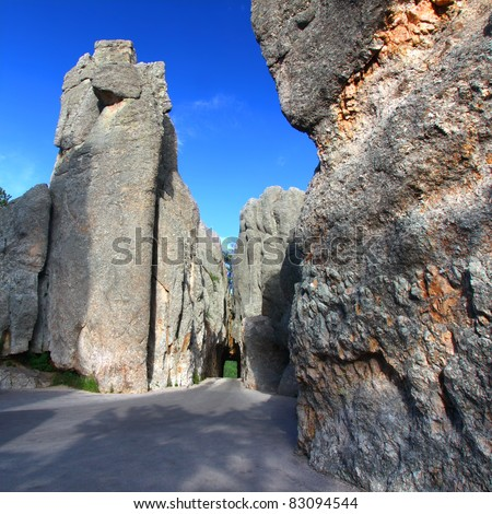 Narrow one lane tunnel through solid rock along the scenic Needles Highway of South Dakota.