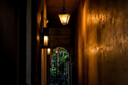 Narrow passageway and nobody in vintage stone dark alley with illuminated lanterns hanging in passage tunnel to garden in evening