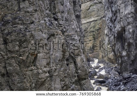 Narrow rocky cliff walls of a glacier gorge river in Grindelwald - Bernese Oberland, Switzerland #769305868