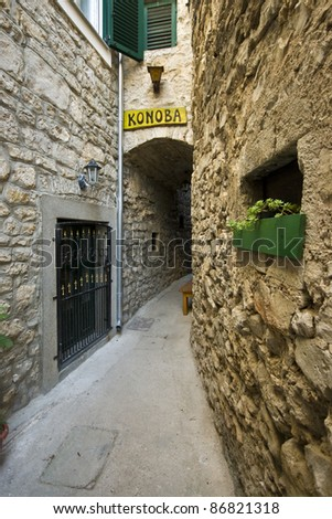 Narrow stone alley with a wooden konoba sign in Vodice