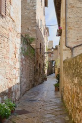 Narrow stone street, ancient walls, Tuscany, Italy. Very beautiful narrow street of pink stone and brick, from the Middle Ages, with a minimum of greenery. Sunny day, the street is bright and joyful.