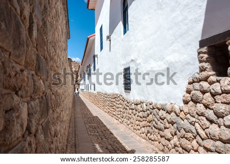 Narrow street alley in Cuzco, Peru with Incan stonework and colonial architecture visible