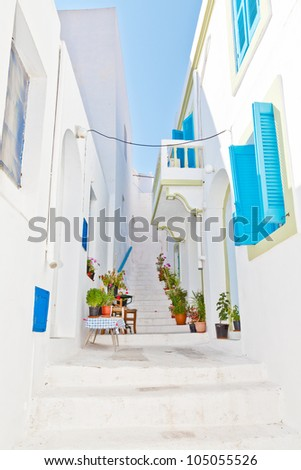 Narrow street in greek city with blue windows - stock photo