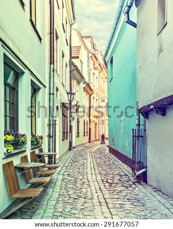 Narrow street in old city of Riga. Image toned in vintage warm colors for inspiration of retro style effect