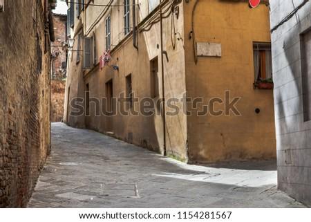 Narrow street in Siena, Italy. #1154281567