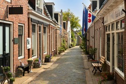 Narrow street in the center of the picturesque village of Woudsen in the province of Friesland, Netherlands.
