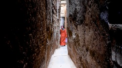 Narrow street. Narrow street in Morocco, a woman is walking at the end of the street.