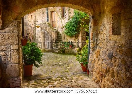 stock photo narrow street of medieval tuff city sorano with arch green plants and cobblestone travel italy 375867613 - Каталог — Фотообои «Балконы, арки»