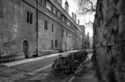 Narrow street or lane with old stone buildings walls, arch doorway and lantern lights. Bicycles and person in distance. Black and white monochrome with diagonal shadows