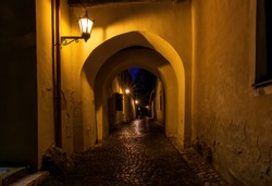 Narrow street with archway in medieval town Spisska Sobota at the night. Poprad city, Slovakia. Popular travel destination