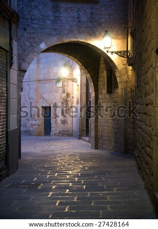 Narrow street with archway in the Old Town of Barcelona, Spain.