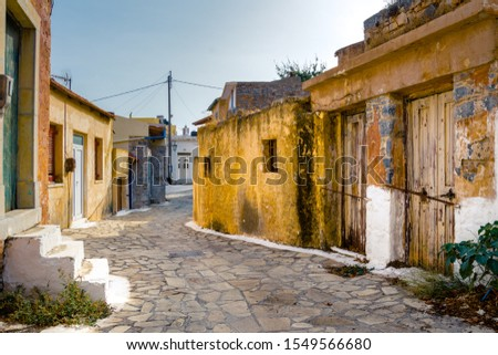 Narrow street with colorful stone houses in the old village of Pano Elounda, Crete, Greece.  #1549566680