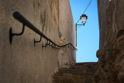 Narrow street with stairs up and a lamppost over the blue sky in the background, Onda, Castellon, Spain