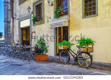 Narrow street with tables of old trattoria in Florence, Tuscany, Italy. Architecture and landmark of Florence. Cozy cityscape of Florence