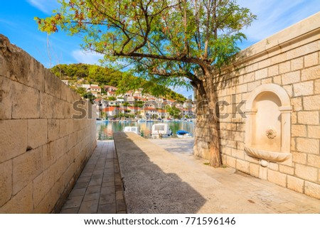 Narrow street with water tap in  Pucisca port with fishing boats, Brac island, Croatia